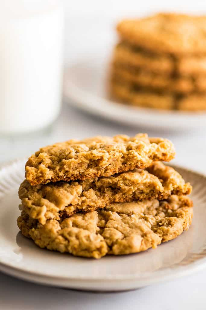 Photo of two peanut butter oatmeal cookies on a plate with a glass of milk.