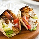Chicken Shawarma With Yogurt Sauce wrapped in foil on a wooden plate.
