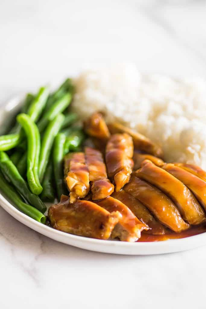 Image of chicken thighs in homemade teriyaki sauce on a plate with green beans and rice.