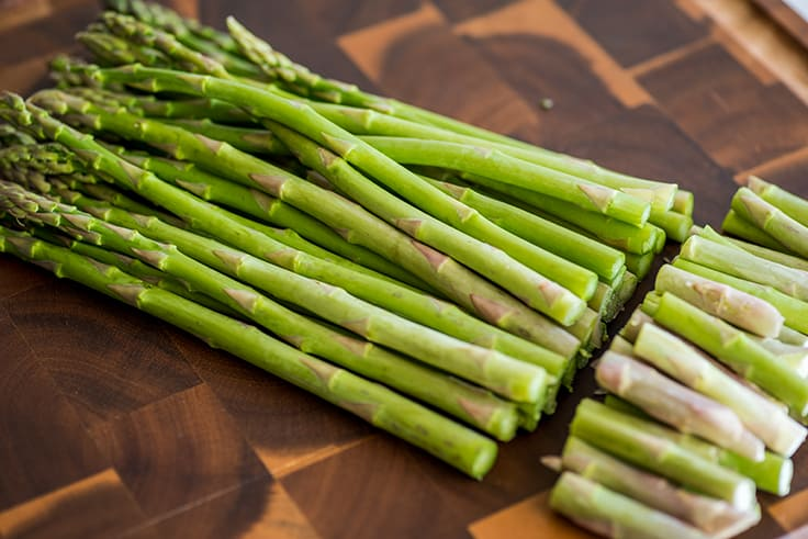 Photo of asparagus on a cutting board with ends trimmed off.