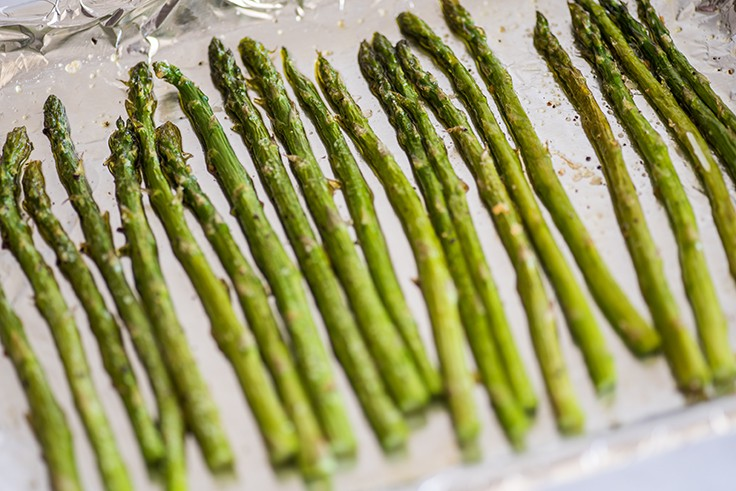 Photo of asparagus cooked in the oven on a cookie sheet.