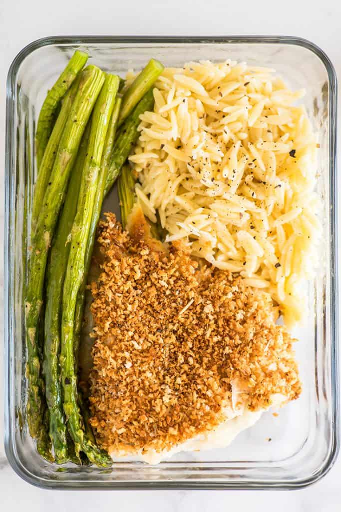 Photo of asparagus cooked in the oven in a meal prep container.