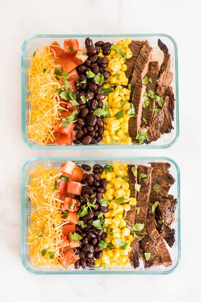 Overhead shot of two meal prep carne asada burrito bowls in glass containers.