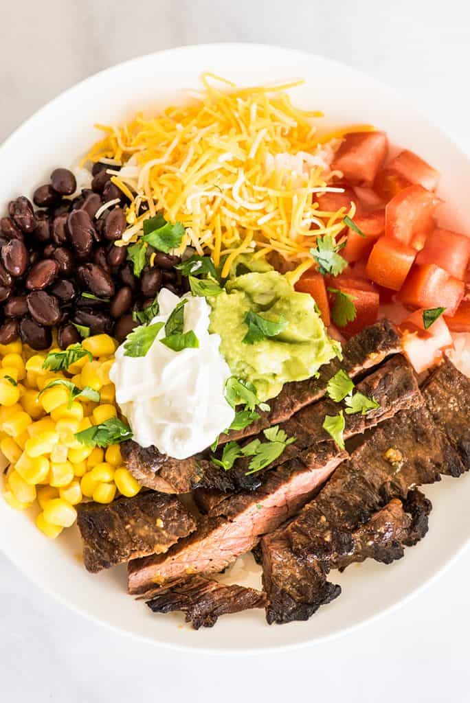Overhead shot of carne asada burrito bowl in a white bowl on marble back drop.
