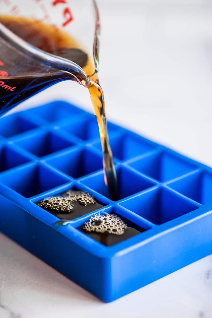 Coffee being poured into mold to make coffee ice cubes.
