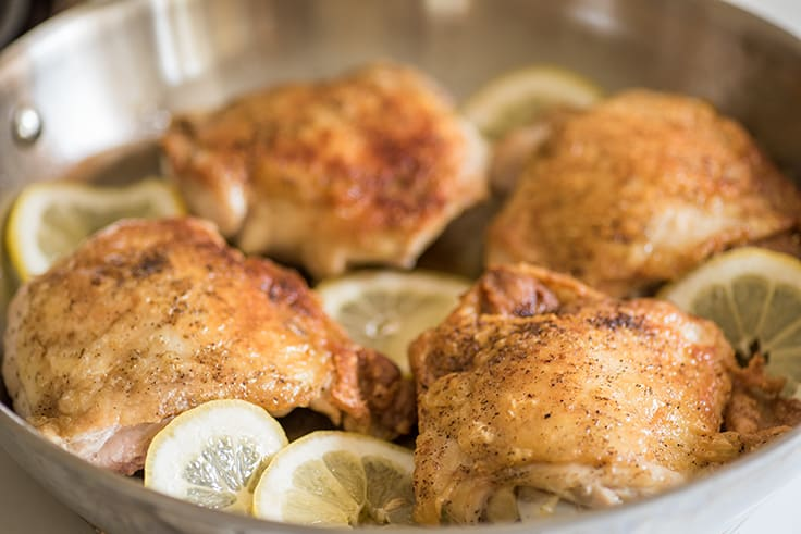 Lemon chicken thighs in skillet.