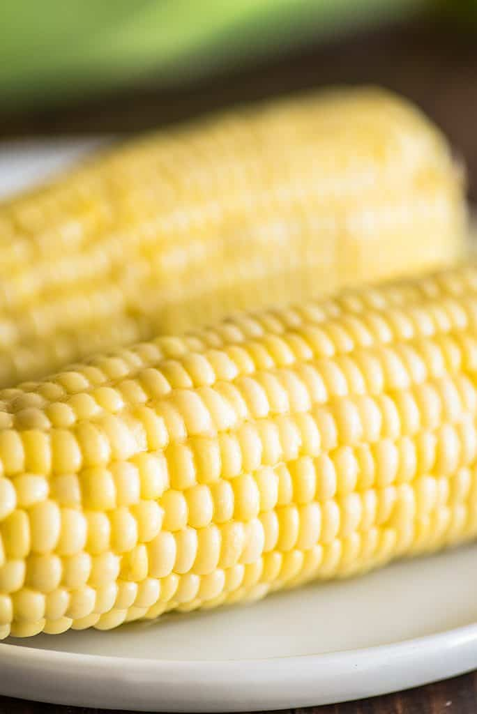 Microwave corn on the cob on a plate.