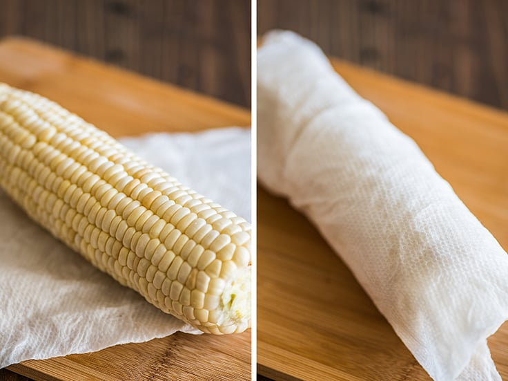 Corn being wrapped in a paper towel to be cooked in the microwave.