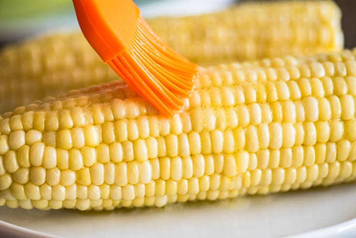 Microwaved corn on the cob being brushed with butter.