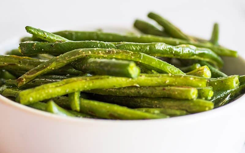Roasted green beans in a white bowl.