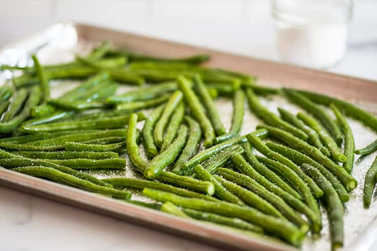 Green beans on a baking sheet before baking.