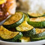Roasted zucchini on a plate with chicken.