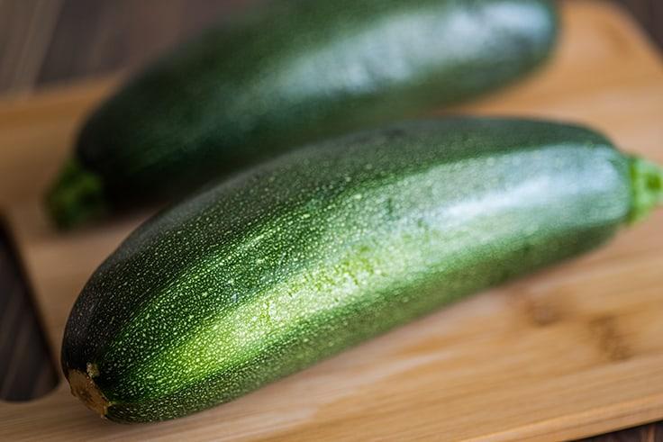 Whole zucchini on a cutting board.