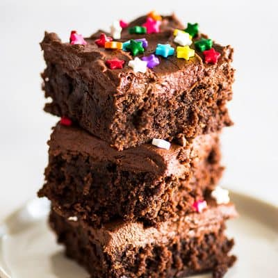 Picture of three frosted brownies stacked on a white plate.