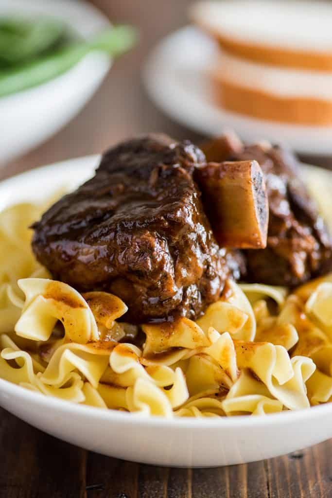 Photo of braised short ribs over egg noodles in a white bowl.