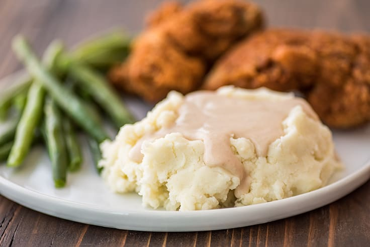 Easy gravy over mashed potatoes on a plate with chicken