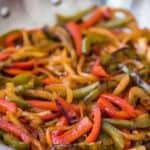 Fajita vegetables in a large skillet.