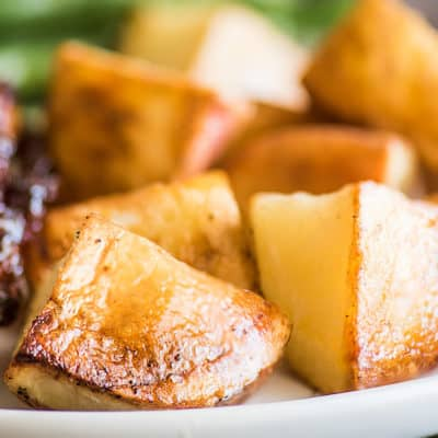 Oven-roasted red potatoes on a white plate.