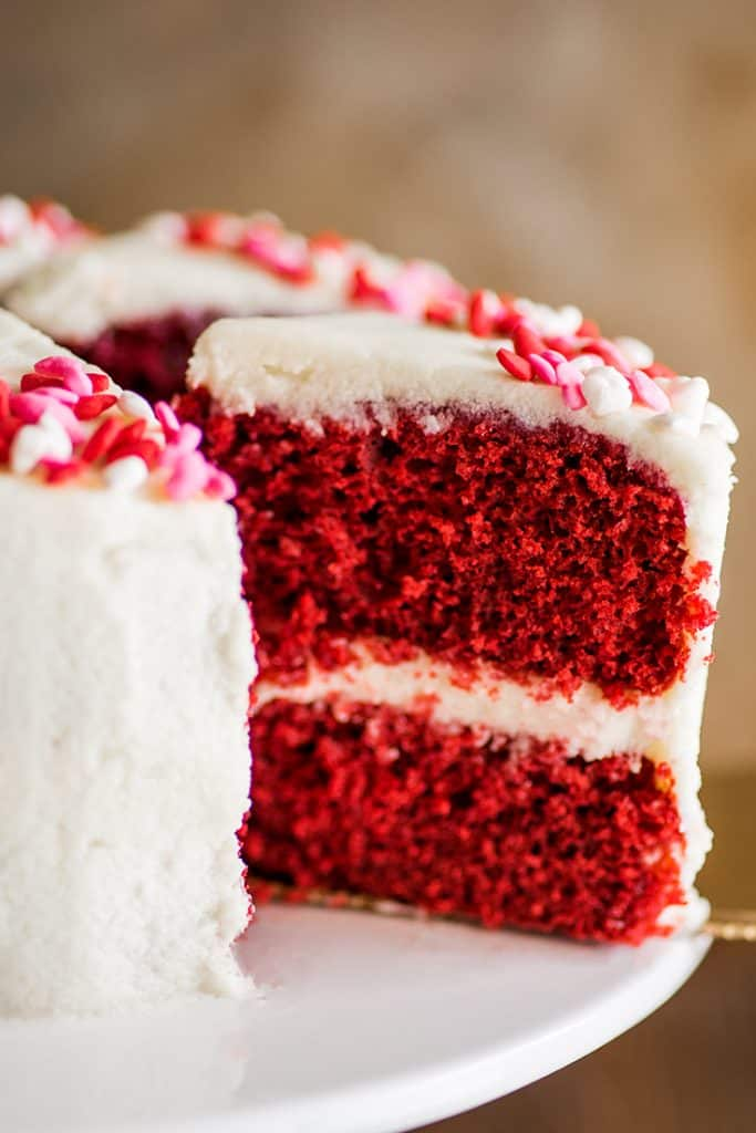 Picture of a slice of six-inch red velvet cake being cut out of the cake.