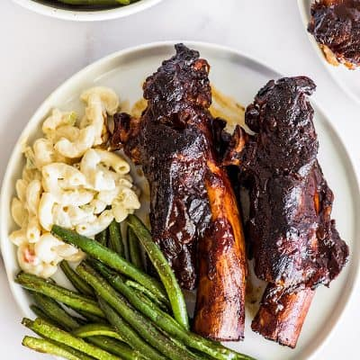 Beef ribs on a plate with pasta salad and green beans.
