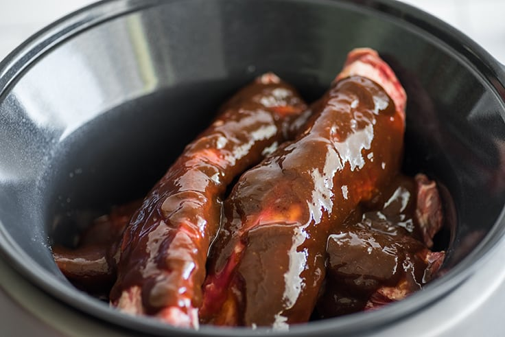 Beef ribs in a slow cooker with barbecue sauce.