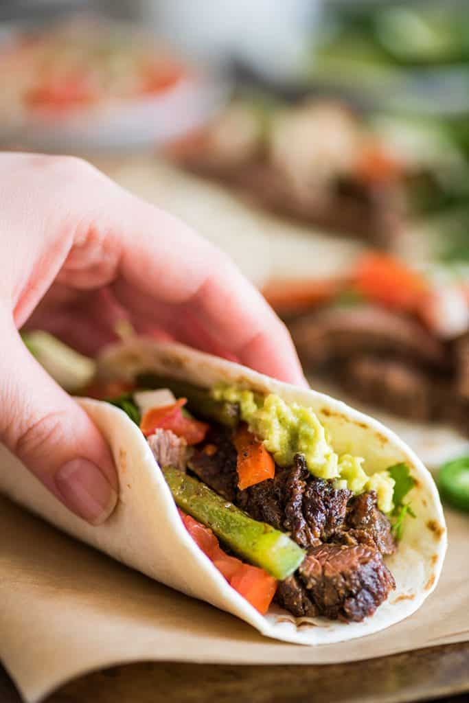 Photo of hand holding steak fajita with guacamole.