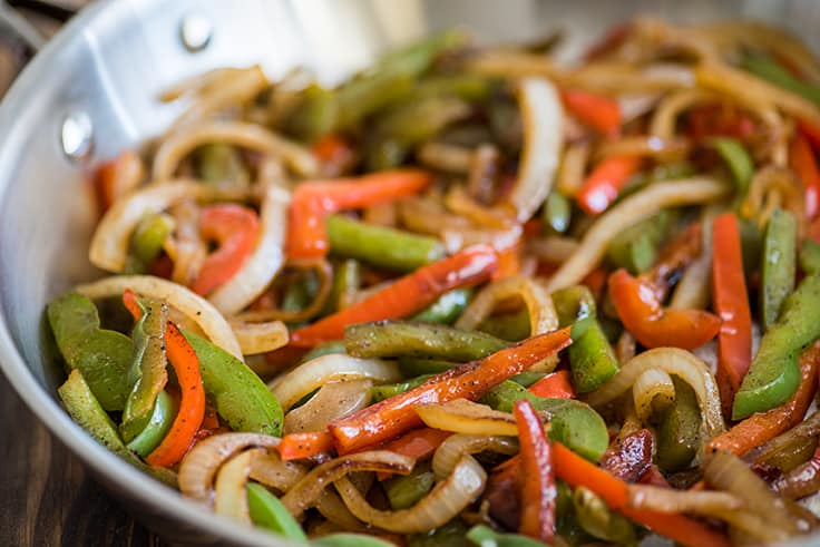 Close up photo of fajita veggies in a pan for steak fajitas.