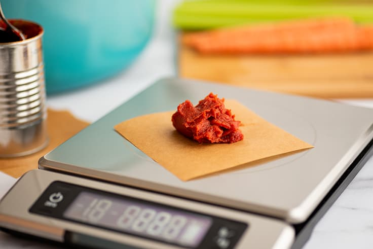 Scoop of tomato paste being weighed for freezing.