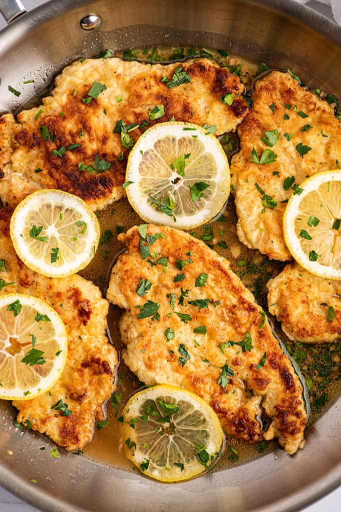 Overhead photo of Chicken Francaise in a pan with lemon slices.