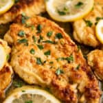 Chicken Francaise in a pan with lemon slices.
