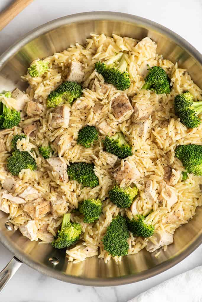 Chicken and orzo with broccoli in a skillet.