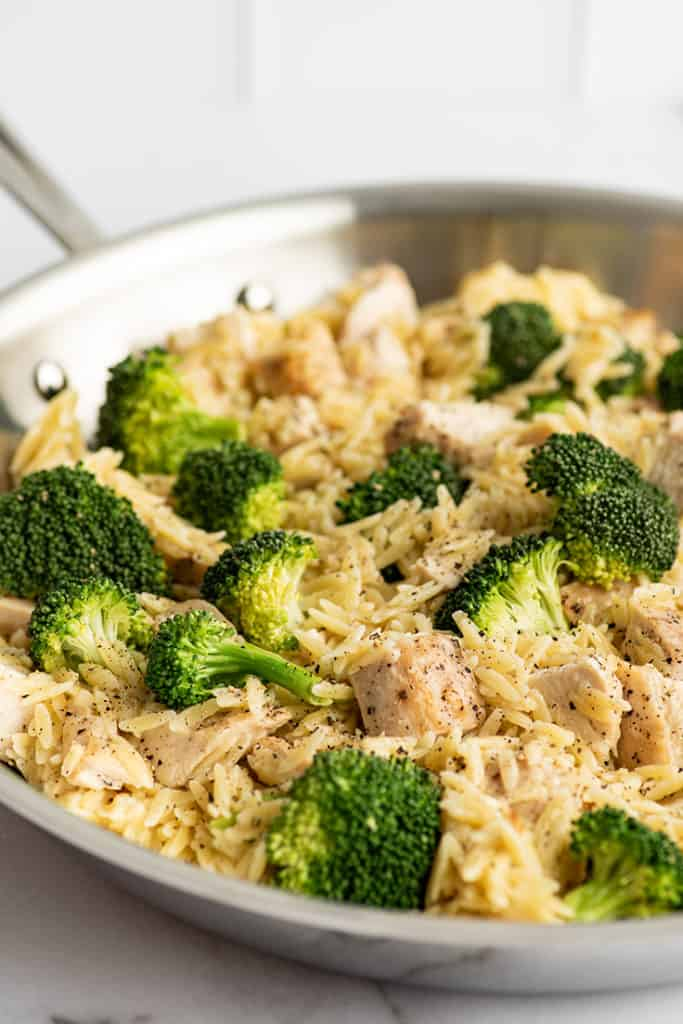 Chicken and broccoli orzo in a skillet.