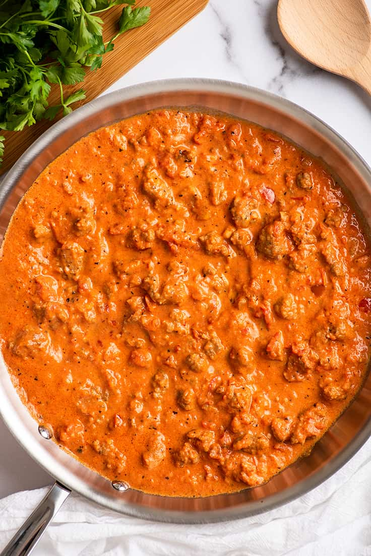 Creamy sausage pasta sauce in a skillet.