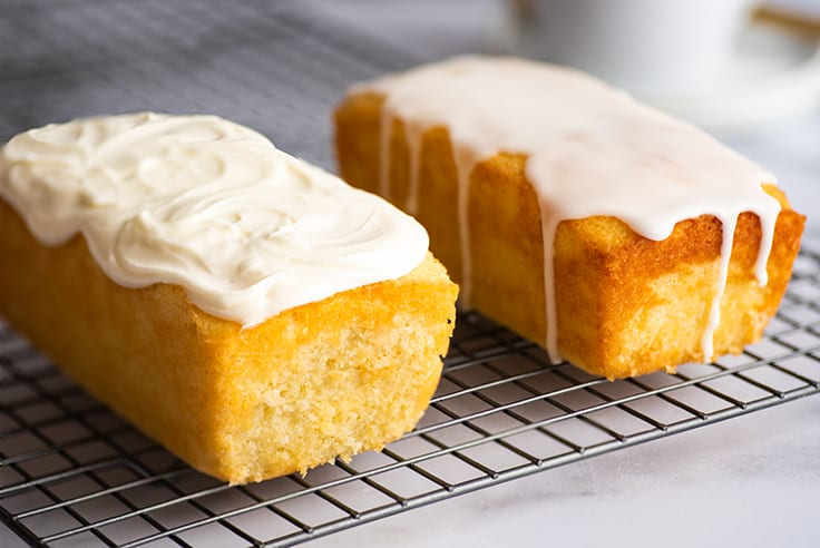 Lemon pound cake with cream cheese glaze on a cooling rack.