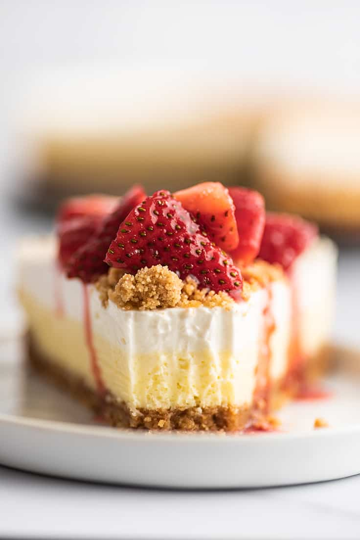Slice of cheesecake with a bite out of it.