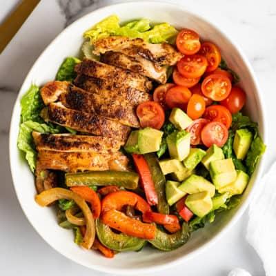 Chicken fajita salad in a white bowl.