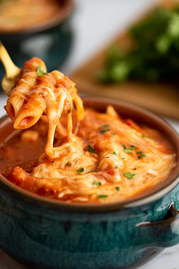 Spoonful of chicken parm soup with melted cheese.