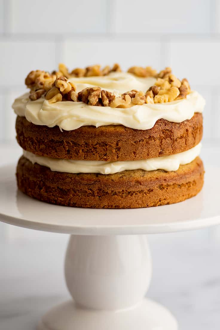Small two layer banana cake with cream cheese frosting on a cake stand.