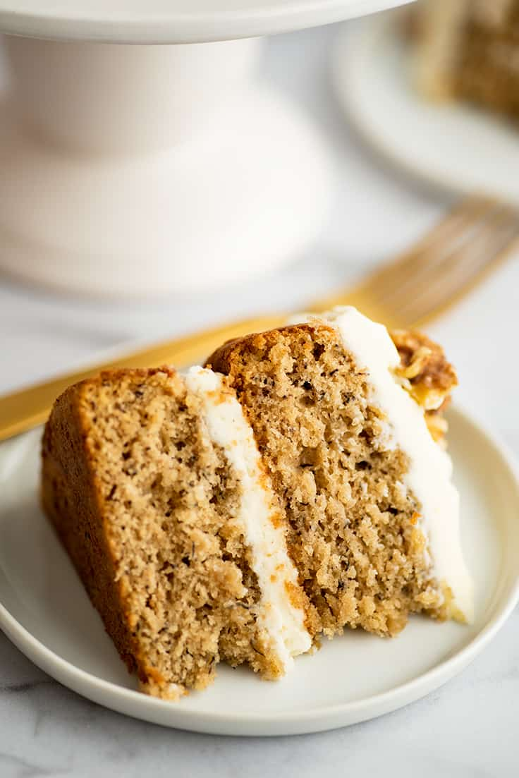 Slice of small two layer banana cake on a plate.