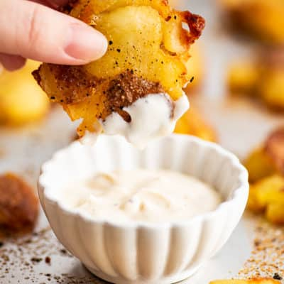 Smashed red potato being dipped in aioli.